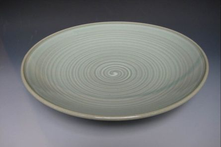 Porcelain plate with slip pattern and celadon glaze
